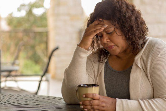 Worried woman holding a mug of. coffee