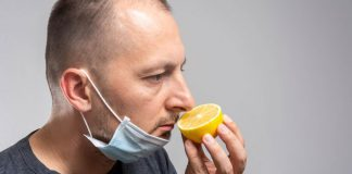 Man with covid smelling an orange