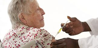 NP giving older woman a flu shot